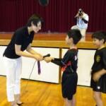 質問をした子供たちへ銅メダルを触らせてあげる迫田さん